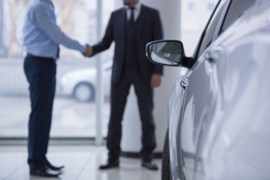 車の前で握手